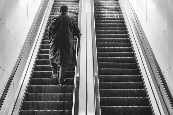 Man Walking Up Escalator Free Photo